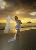 Mädchen auf Strand bei Sonnenaufgang Stockbilder
