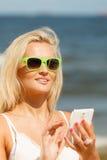 Mädchen auf Strand mit Telefon Stockbilder