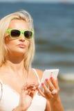 Mädchen auf Strand mit Telefon Lizenzfreies Stockbild