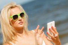 Mädchen auf Strand mit Telefon Stockfoto