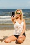 Mädchen auf Strand mit Telefon Stockfotos