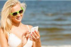Mädchen auf Strand mit Telefon Stockbild