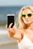 Mädchen auf Strand mit Telefon Lizenzfreies Stockfoto