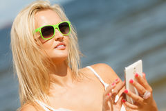 Mädchen auf Strand mit Telefon Stockfotografie