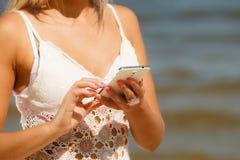 Mädchen auf Strand mit Telefon Lizenzfreie Stockfotografie