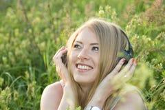 Mädchen auf Wiese hörend Musik Stockfotografie