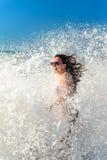 Mädchen badet in einem Sturm in Meer, Gelächter, Freude Stockbild