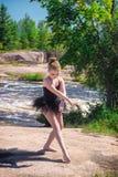 Mädchen-Ballerina, die draußen durch Fluss aufwirft Stockbilder