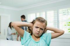 Mädchen bedeckt ihre Ohren mit ihren Händen während die Eltern, die im Hintergrund argumentieren stockfotografie