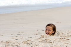 Mädchen begraben im Sand Lizenzfreie Stockfotos