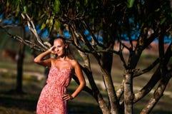 Mädchen bei dem Sonnenuntergang, der nahe einem tropischen Baum steht stockfoto