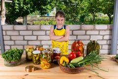Mädchen bei Tisch mit Gemüse und Konserven stockbilder