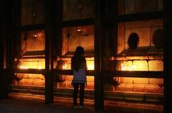 Mädchen beleuchtet Gebets-Kerzen an der Kirche des heiligen Grabes, Jerusalem, Israel Stockbild