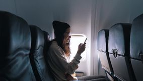 Mädchen benutzt einen Smartphone während des Fluges stock footage