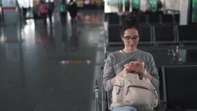 Mädchen benutzt Smartphone im Flughafenaufenthaltsraum stock video footage