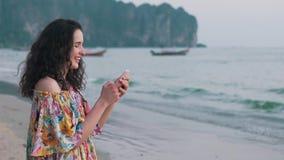 Mädchen benutzt Smartphone nahe dem Ozean stock footage