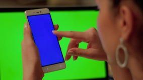 Mädchen berührt Telefon mit blauem Schirm stock footage