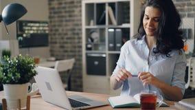 Mädchen beschäftigt mit Laptop im Büro, das den Schirm betrachtend sitzt am Schreibtisch grast stock video