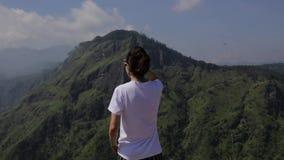 Mädchen betrachtet das Tal von einer Spitze stock video footage