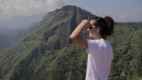 Mädchen betrachtet das Waldtal von einer Spitze stock footage