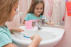 Mädchen, bevor die Zähne gesäubert werden, die Zahnpasta aus einem Rohr auf Zahnbürste heraus zusammendrücken stockfoto