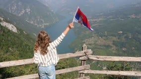 Mädchen bewegt mit einer serbischen Flagge auf dem Berg Tara wellenartig stock video footage