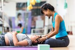 Mädchen bildete Yoga für Entspannung nah durch Yogalehrer am Yogastudio in Bangkok, Thailand aus stockfotos