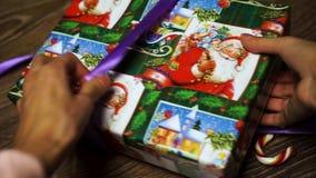 Mädchen bindet einen Bogen auf dem Geschenk los stock video