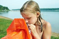 Mädchen bläst orange Matratze auf Strand auf Stockfotografie