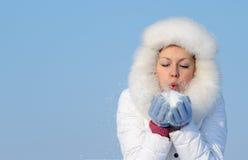 Mädchen bläst Schneeflocken von der Hand ab stockfotografie