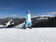 Mädchen in blauem, rosa Einhornpyjama kigurumi im Freien mit Snowboard auf dem Skibericht in den Schneebergen Lizenzfreies Stockbild