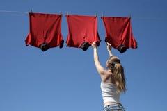 Mädchen, blauer Himmel und rote Wäscherei Stockfotografie