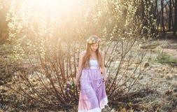 Mädchen, Blumenkranz und Frühlingswald Stockbild