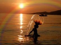 Mädchen, Boot und Regenbogen im Sonnenuntergang Stockfoto