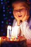 Mädchen brennt heraus die Kerzen auf dem Kuchen durch Stockbilder