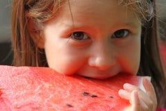 Mädchen Brunette isst eine enorme Scheibe der roten Wassermelone Lizenzfreie Stockfotos