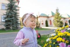 Mädchen am bunten Blumenbeet Lizenzfreie Stockbilder