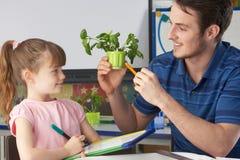 Mädchen, das über Anlagen mit Lehrer erlernt stockbild