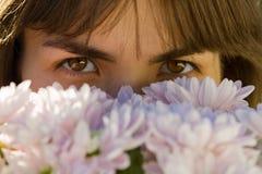 Mädchen, das über einem Blumenstrauß (Nahaufnahme, schaut) Stockfotografie