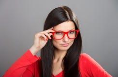 Mädchen, das über Gläsern schaut Stockfotografie
