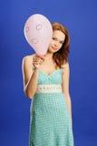 Mädchen, das über rosafarbenem überraschtem Ballon blickt Stockfotografie