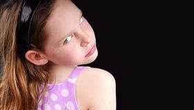 Mädchen, das über Schulter schaut Stockbild