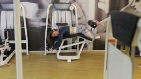 Mädchen, das Übung für Beine auf einer Pressemaschine in der Turnhalle tut stock video