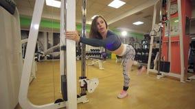 Mädchen, das Übung für Beine auf einer Pressemaschine in der Turnhalle tut stock video footage