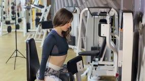 Mädchen, das Übung für Beine auf einer Pressemaschine in der Turnhalle tut stock footage