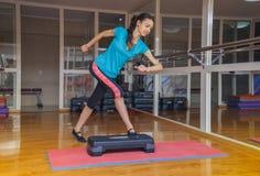 Mädchen, das Übungen eine Schrittplattform in der Turnhalle, gesunder Lebensstil tut Stockbild