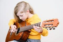 Mädchen, das acustic Gitarre spielt Stockfotografie