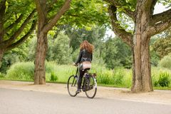Mädchen, das in das Amsterdam Vondelpark radfährt Stockfotos