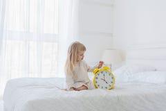 Mädchen, das analogen Wecker im Schlafzimmer hält Lizenzfreie Stockfotos
