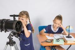 Mädchen, das Astronom den Himmel durch ein Teleskop, das andere Mädchen betrachtet, sitzt am Tisch Lizenzfreies Stockfoto